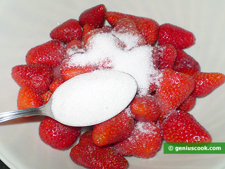 berries in a bowl with a sugar on top
