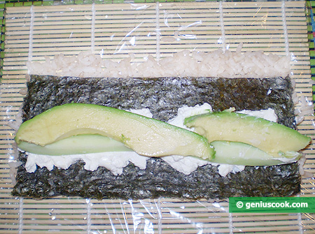 On a sheet of nori Philadelphia cheese, slices of avocado and cucumber
