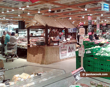 In the center, farmer's store hut. He cuts you prosciutto thinly