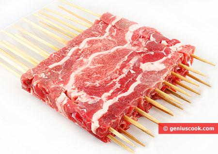 Sliced meat on skewers for arrosticini